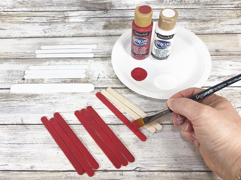 Paint craft sticks red and white Creatively Beth #creativelybeth #drseusscraft #catinthehatcraft #craftsticks #popsiclesticks #catinthehat #drseuss