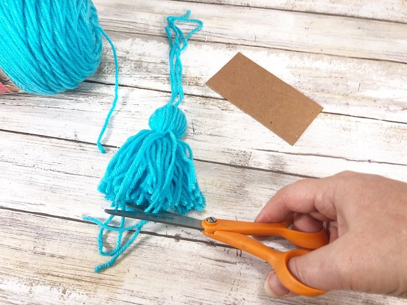 Trim the ends of the yarn tassel to finish Creatively Beth #creativelybeth #drseuss #freeprintable #thing1andthing2 #bookmarks #catinthehat #readacrossamericaweek