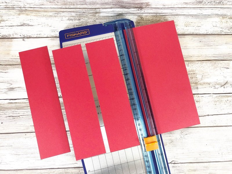 Trim red cardstock for Dr. Seuss Bookmarks Creatively Beth #creativelybeth #drseuss #freeprintable #thing1andthing2 #bookmarks #catinthehat #readacrossamericaweek