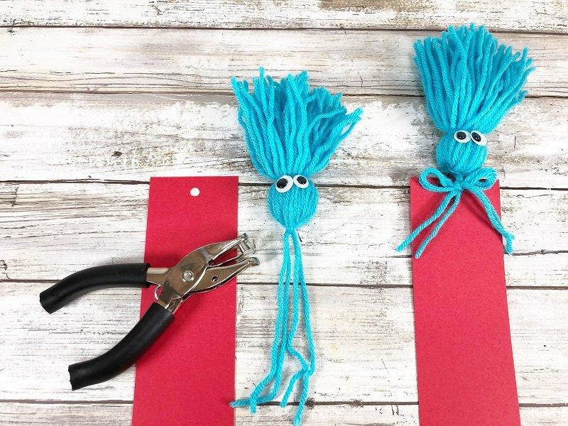 Punch hole and attach tassel to the top of the bookmark Creatively Beth #creativelybeth #drseuss #freeprintable #thing1andthing2 #bookmarks #catinthehat #readacrossamericaweek