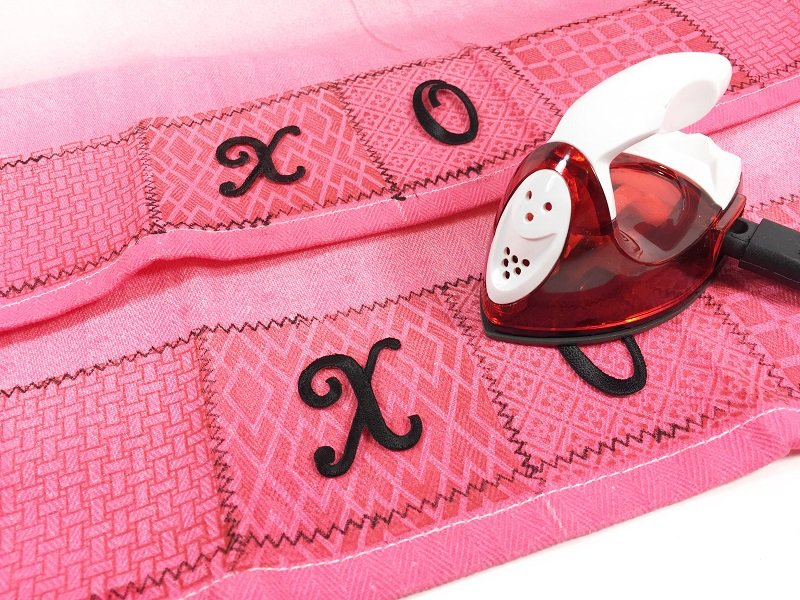 Iron on embroidered letters to spell out a message Hugs and Kisses Kitchen Towels for Valentine's Day Creatively Beth #creativelybeth #valentinesday #crafts #hugsandkisses