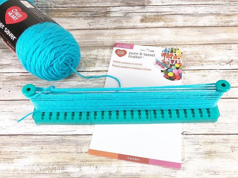 Create yarn pom poms with turquoise yarn Creatively Beth #creativelybeth #pompomcraft #lovebug #drseuss #catinthehat #thing1andthing2 #pompomcraft