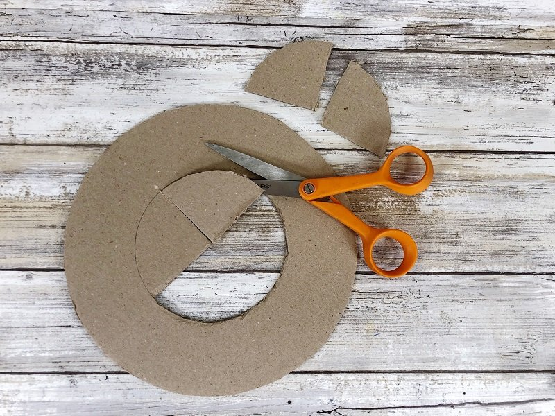 Poke a hole in the center of the wreath circle and then cut out the middle by Creatively Beth #creativelybeth #dollartreecrafts #easterwreath #dollartreecarrots #springwreath