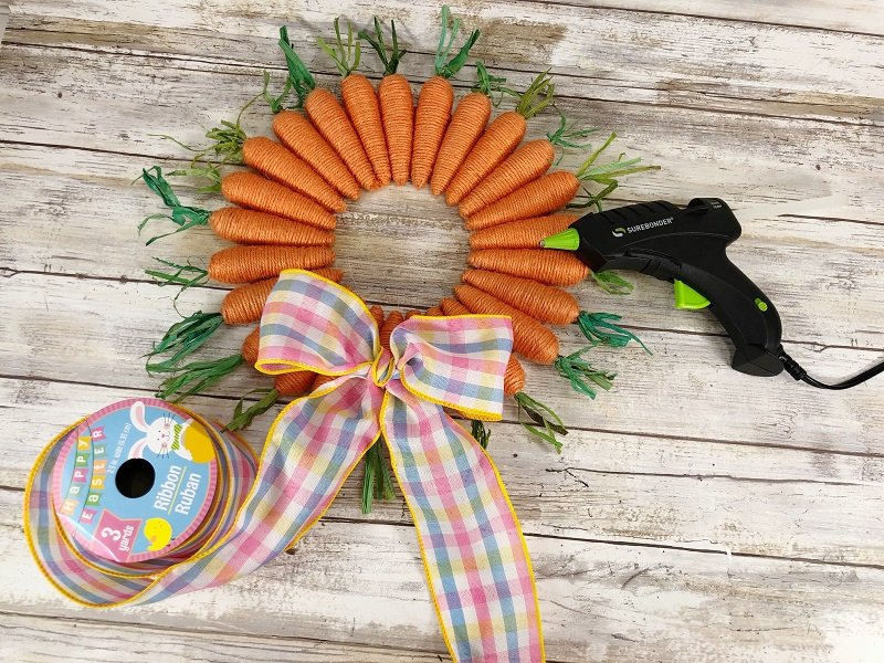 Tie a bow with pastel plaid wired ribbon also from Dollar Tree by Creatively Beth #creativelybeth #dollartreecrafts #easterwreath #dollartreecarrots #springwreath