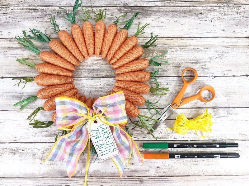 Using skinny yellow ribbon tie tag onto bow by Creatively Beth #creativelybeth #dollartreecrafts #easterwreath #dollartreecarrots #springwreath