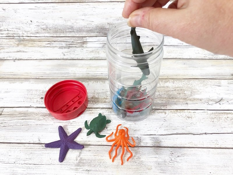 Layer the plastic animals in the sensory bottle with the Poly-Pellets by Creatively Beth #creativelybeth #sensorybottle #freeprintable #wordsearch #doodles #madewithFFW